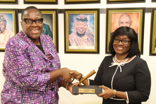 L – R shows Ms. Tinuade Awe, Executive Director, Regulation, The Nigerian Stock Exchange (NSE) presenting a replica of the closing gong to Mrs. Aderonke Adedeji, President, Pension Fund Operators Association of Nigeria and CEO Leadway Pensure during a Closing Gong Ceremony at the Exchange.