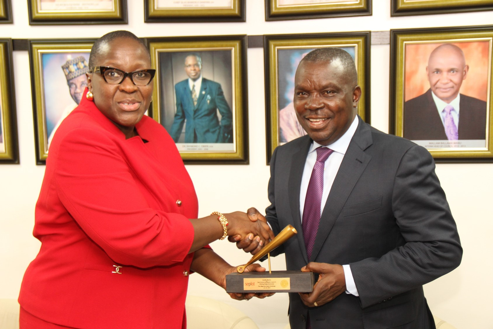 L – R show Ms. Tinuade Awe, Executive Director, Regulation, The Nigerian Stock Exchange (NSE) presenting a replica of the closing gong to Austin Avuru, Chief Executive Officer, Seplat Petroleum Development Company Plc during a Facts Behind the Figures presentation at the Exchange today