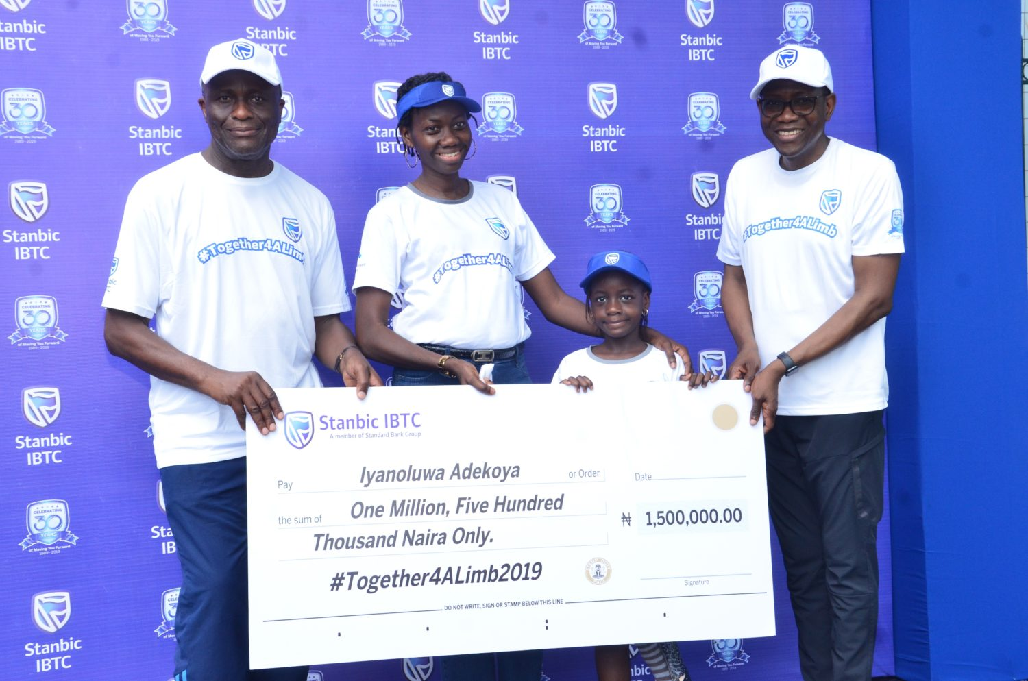 L-R: Dr. Adeyemi Omobowale, Chief Executive Officer, Reddington Hospital Group; Mrs. Ruth Adekoya, mother of the beneficiary; Iyanuoluwa Adekoya, Together4ALimb 2019 beneficiary and Yinka Sanni, Chief Executive, Stanbic IBTC Holdings PLC; during the presentation of EduTrust funds to beneficiaries at the 2019 edition of the Together4alimb Walk, organized by Stanbic IBTC Holdings.