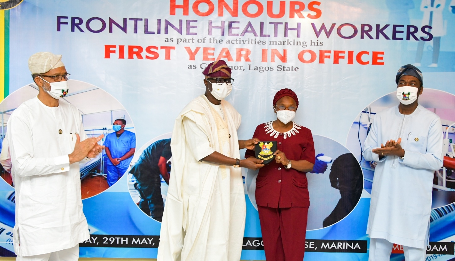 L-R: Lagos State Commissioner for Health, Prof. Akin Abayomi; Governor Babajide Sanwo-Olu, presenting a plaque to a Frontline Health worker, Mrs. Basirat Adeoye - Apex Nurse of Mainland Hospital Yaba and the Deputy Governor, Dr. Obafemi Hamzat during the Governor's award presentation to Frontline Health workers as part of activities to commemorate his administration's First Year in Office House, at Lagos House, Marina, on Friday, May 29, 2020.