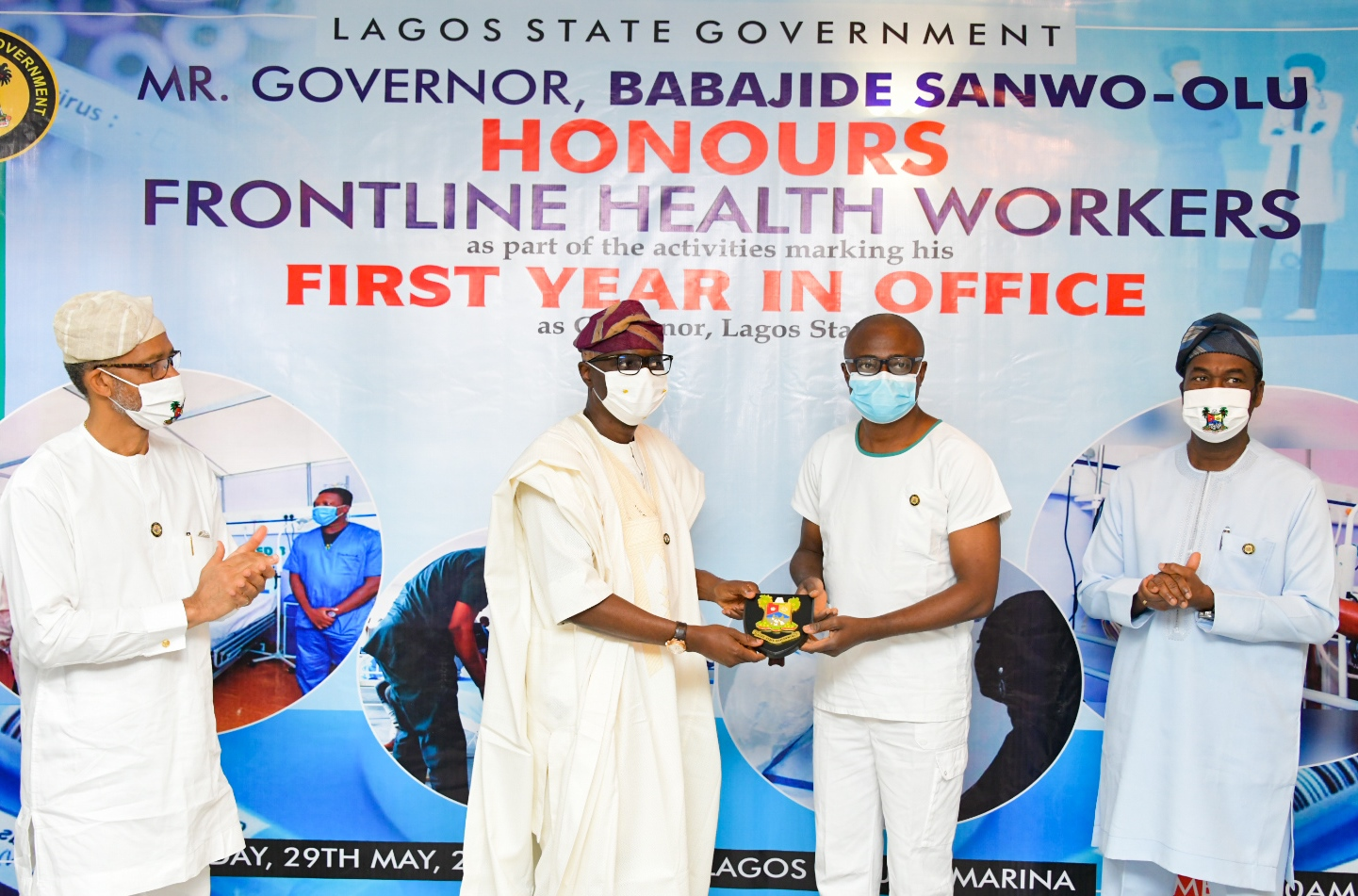 L-R: Lagos State Commissioner for Health, Prof. Akin Abayomi; Governor Babajide Sanwo-Olu, presenting a plaque to a Frontline Health worker, Dr. Sunday Oluseyi Adesola - Principal Medical Officer 1 at Isolation Centre, Mainland Hospital Yaba, and the Deputy Governor, Dr. Obafemi Hamzat during the Governor's award presentation to Frontline Health workers as part of activities to commemorate his administration's First Year in Office, at Lagos House, Marina, on Friday, May 29, 2020.