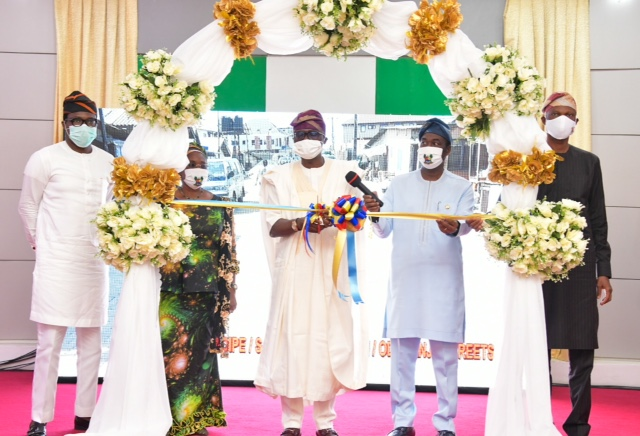 Lagos State Governor, Mr. Babajide Sanwo-Olu (middle), cutting the tape to commission vital and various project (Classroom blocks in different Primary and Secondary Schools; Housing Schemes at Igbogbo-Ikorodu and Topo-Badagry; Intelligent Transportation System (ITS) for Bus Reform Scheme at different bus terminals; rehabilitated roads in LGs and Concrete jetty with shoreline protection at Baiyeku, Ikorodu) to commemorate his administration's First Year in Office, at Lagos House, Marina, on Friday, May 29, 2020. With him: Deputy Governor, Dr. Obafemi Hamzat (second right); Chief of Staff to the Governor, Mr. Tayo Ayinde (right); Secretary to the State Government, Mrs. Folasade Jaji (second left) and the Head of Service, Mr. Hakeem Muri-Okunola (left).