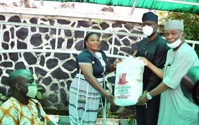 Oyo State Governor, Engr Seyi Makinde (second right); being assisted by Commissioner for Special Duties, Chief Bayo Lawal (right) presenting palliative material to Funke Adegoke during the symbolic distribution of Palliatives to People living with disabilities held at Governor's Office, Ibadan. PHOTO: Oyo State Government.