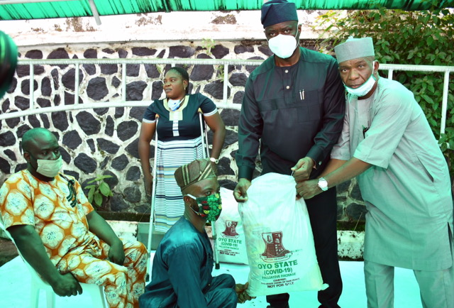 Oyo State Governor, Engr Seyi Makinde (second right); being assisted by Commissioner for Special Duties, Chief Bayo Lawal (right) presenting palliative material to Mr Ibeh Chukwuma during the symbolic distribution of Palliatives to People living with disabilities held at Governor's Office, Ibadan. PHOTO: Oyo State Government.