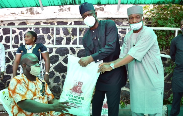 Oyo State Governor, Engr Seyi Makinde (middle); being assisted by Commissioner for Special Duties, Chief Bayo Lawal (right) presenting palliative material to Mr Oyayinka Babawale during the symbolic distribution of Palliatives to People living with disabilities held at Governor's Office, Ibadan. PHOTO: Oyo State Government.