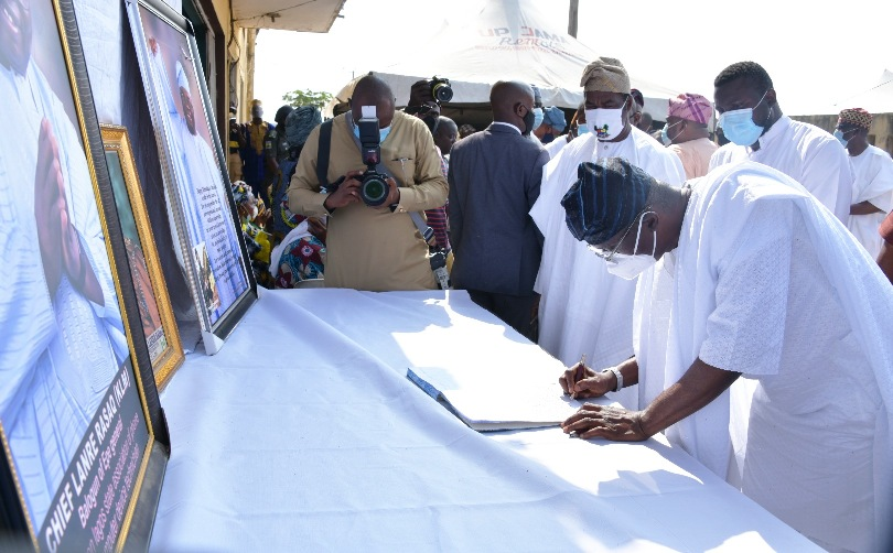 Lagos State Governor, Mr. Babajide Sanwo-Olu (right), signing the condolence register of Late Chief Lanre Razak during his visit to the family of the deceased on Sunday, August 16, 2020. With him are: Son of the deceased, Mr. Ibrahim Razak (middle) and Lagos Deputy Governor, Dr. Obafemi Hamzat (left).